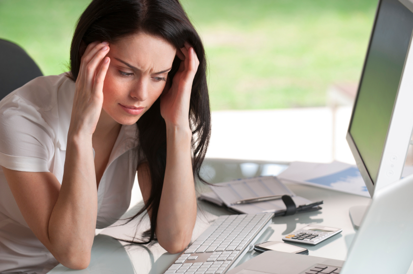 Attractive woman holding her head sitting at her desk